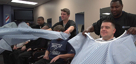 Genesis Career College's master barber students practice putting on haircut capes