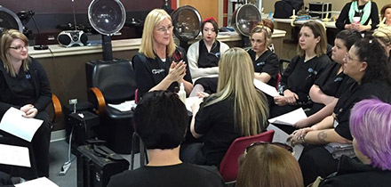 Students circled around instructor in hair salon at Genesis Career College