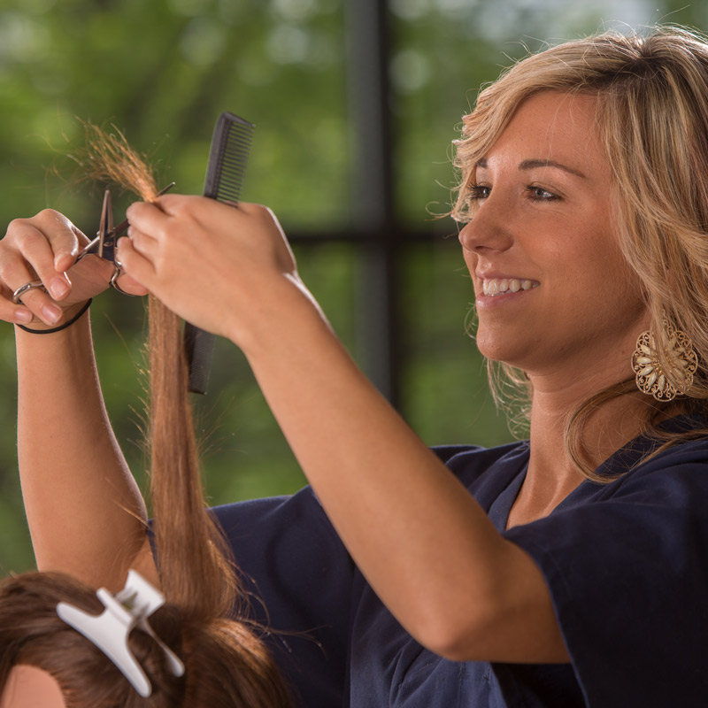 Genesis Career College cosmetology student practicing cutting hair.