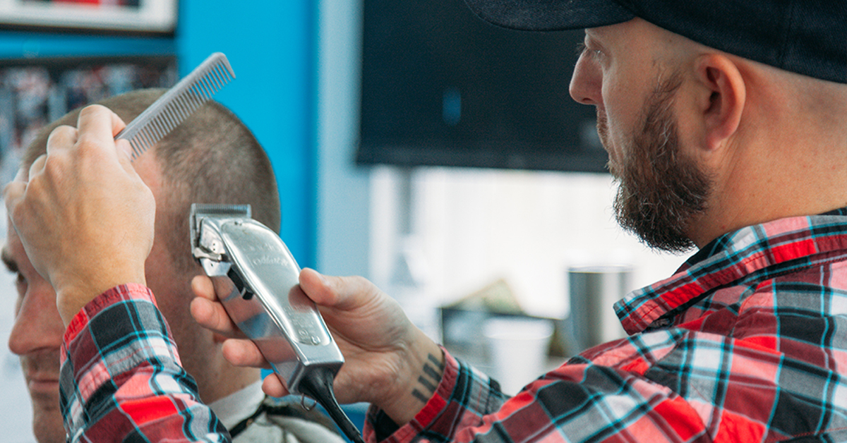Barber performing haircut on man with buzzcut