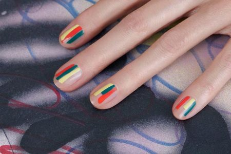 Woman's hand with stripe manicure utilizing negative space