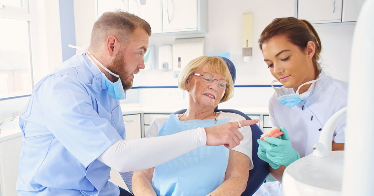 Two young dental assistants advising an older woman on denture options