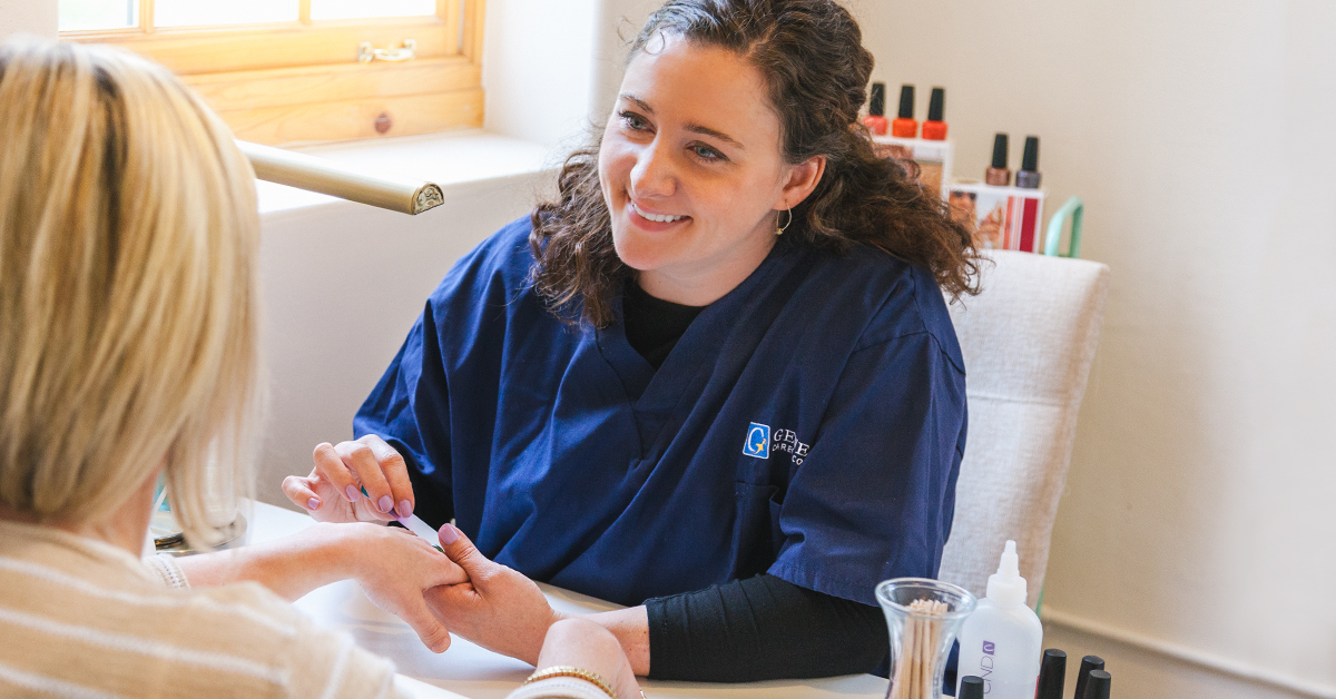 Smiling nail tech giving a manicure