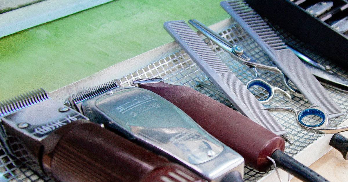Clippers, scissors, and other barber tools all lined up on counter.